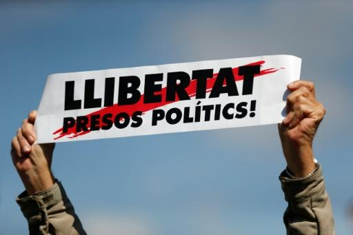 A man holds a placard reading 'Free political prisoners' during a protest called by Catalan pro-independence demonstrators