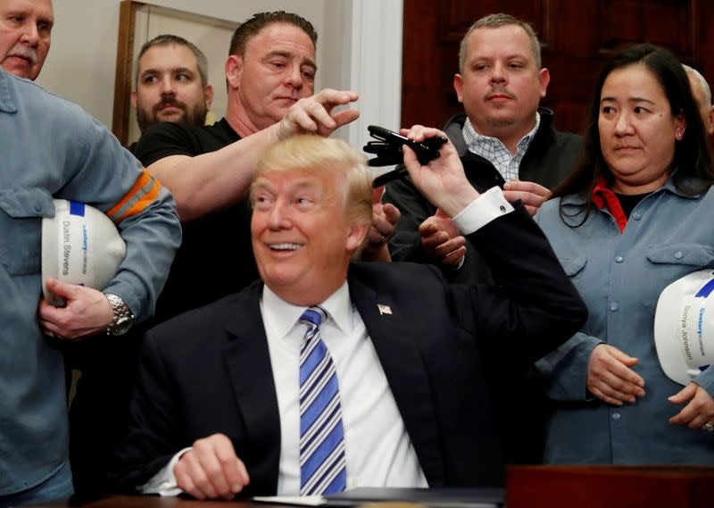 FILE PHOTO: FILE PHOTO: U.S. President Donald Trump signs a presidential proclamation placing tariffs on steel and aluminum imports while surrounded by workers from the steel and aluminum industries at the White House in Washington