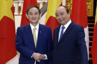 Japanese Prime Minister Yoshihide Suga, left, and his Vietnamese counterpart Nguyen Xuan Phuc shake hands at the Government Office in Hanoi, Vietnam Monday, Oct. 19, 2020. (Luong Thai Linh/Pool Photo via AP)