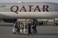 Taliban fighters walk past a Qatar Airways aircraft at the airport in Kabul, Afghanistan, Thursday, Sept. 9, 2021. Some 200 foreigners, including Americans, flew out of Afghanistan on an international commercial flight from Kabul airport on Thursday, the first such large-scale departure since U.S and foreign forces concluded their frantic withdrawal at the end of last month. (AP Photo/Bernat Armangue)