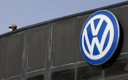 A worker wearing a protective mask stands next to a Volkswagen logo at a dealership in Madrid