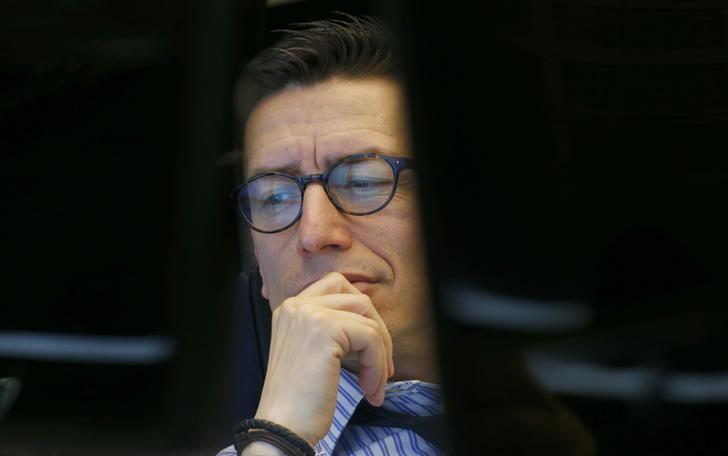 A trader reacts in front of his screens at the Frankfurt stock exchange
