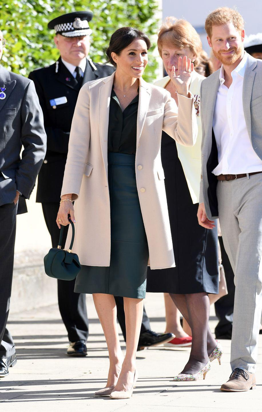 <p>For her inaugural visit to Sussex, Meghan wore a cream-colored Georgia Armani coat over a green leather Hugo Boss skirt and & Other Stories blouse. She also carried a small green top-handled bag.</p>