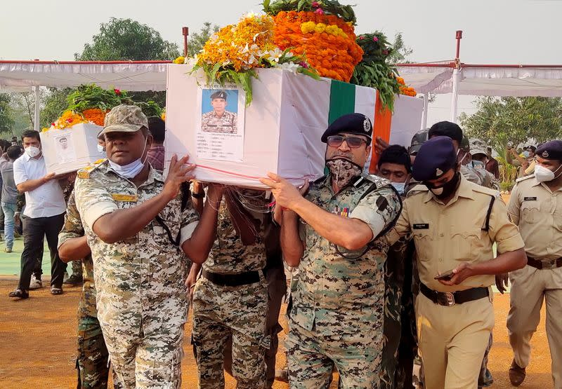 Security forces officers carry the body of a colleague, who was killed in an attack by Maoist fighters, during a wreath laying ceremony in Bijapur