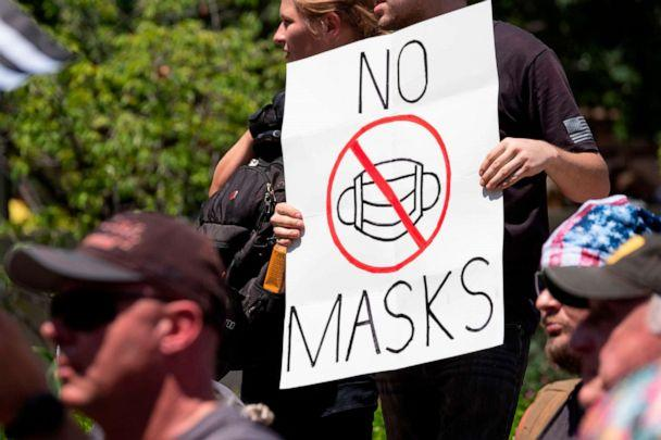 PHOTO: An anti-mask protestor holds up a sign in front of the Ohio Statehouse during a right-wing protest 'Stand For America Against Terrorists and Tyrants' at State Capitol on July 18, 2020 in Columbus, Ohio. (Jeff Dean/AFP via Getty Images)