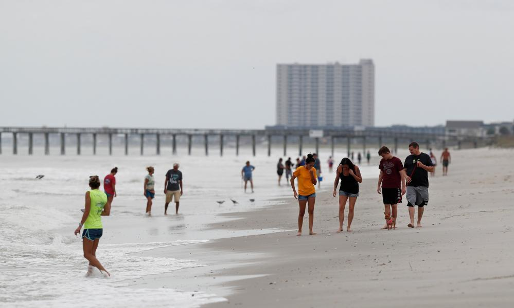 "<span class=""element-image__caption"">People walk on the beach ahead of the arrival of Hurricane Florence in Myrtle Beach, South Carolina, on Thursday.</span> <span class=""element-image__credit"">Photograph: Randall Hill/Reuters</span>"