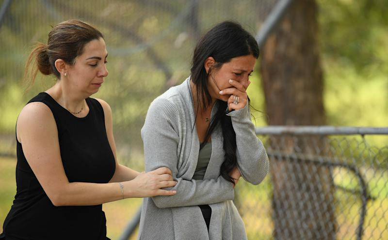 The victims' mother Leila Geagea (right) pauses near flowers placed at the scene where seven children were hit on a footpath by a four-wheel drive in the Sydney suburb of Oatlands on Sunday.