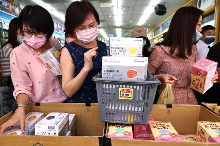 People buy boxes of protective face masks following the outbreak of coronavirus disease (COVID-19), in Taipei,
