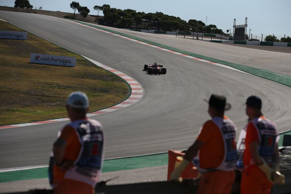 Track marshals watch Ferrari's German driver Sebastian Vettel during the third practice session at the Autodromo Internacional do Algarve on October 24, 2020 in Portimao ahead of the Portuguese Formula One Grand Prix. (Photo by JOSE SENA GOULAO / POOL / AFP) (Photo by JOSE SENA GOULAO/POOL/AFP via Getty Images)