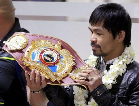 Filipino boxing champion Manny Pacquiao looks at his WBO championship belt after defeating Timothy Bradley, upon his arrival at the Ninoy Aquino International Airport in Manila April 14, 2016. REUTERS/Romeo Ranoco   Picture Supplied by Action Images