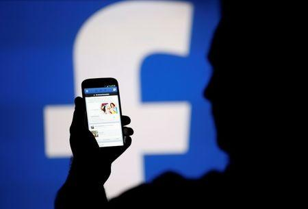 A man is silhouetted against a video screen with an Facebook logo as he poses with an Samsung S4 smartphone in this photo illustration taken in the central Bosnian town of Zenica, August 14, 2013. REUTERS/Dado Ruvic