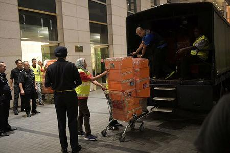 A Malaysian police officer pushes a trolley during a raid of three apartments in a condominum owned by former Malaysian prime minister Najib Razak's family, in Kuala Lumpur