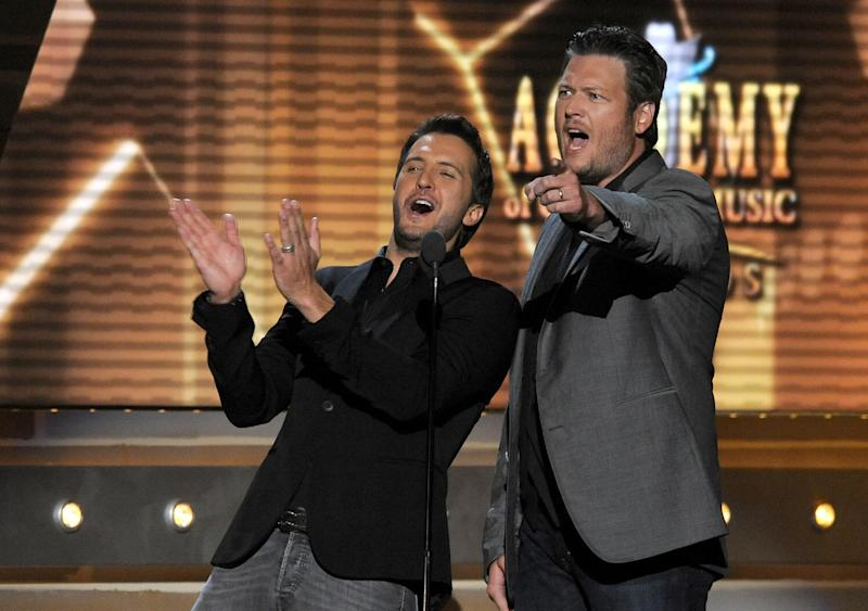 FILE - In this April 7, 2013 file photo, Luke Bryan, left, and Blake Shelton speak on stage at the 48th Annual Academy of Country Music Awards at the MGM Grand Garden Arena in Las Vegas. The 2014 Academy of Country Music Awards in Las Vegas will air live Sunday night, April 6, 2014, from 8-11 p.m. EDT on CBS. Several awards, including top honor entertainer of the year, will be announced during the broadcast, to be hosted by Blake Shelton and Luke Bryan. Shelton, Bryan, George Strait, Miranda Lambert, Jason Aldean, Keith Urban, Tim McGraw, Shakira and Stevie Nicks are scheduled to perform. (Photo by Chris Pizzello/Invision/AP, File)