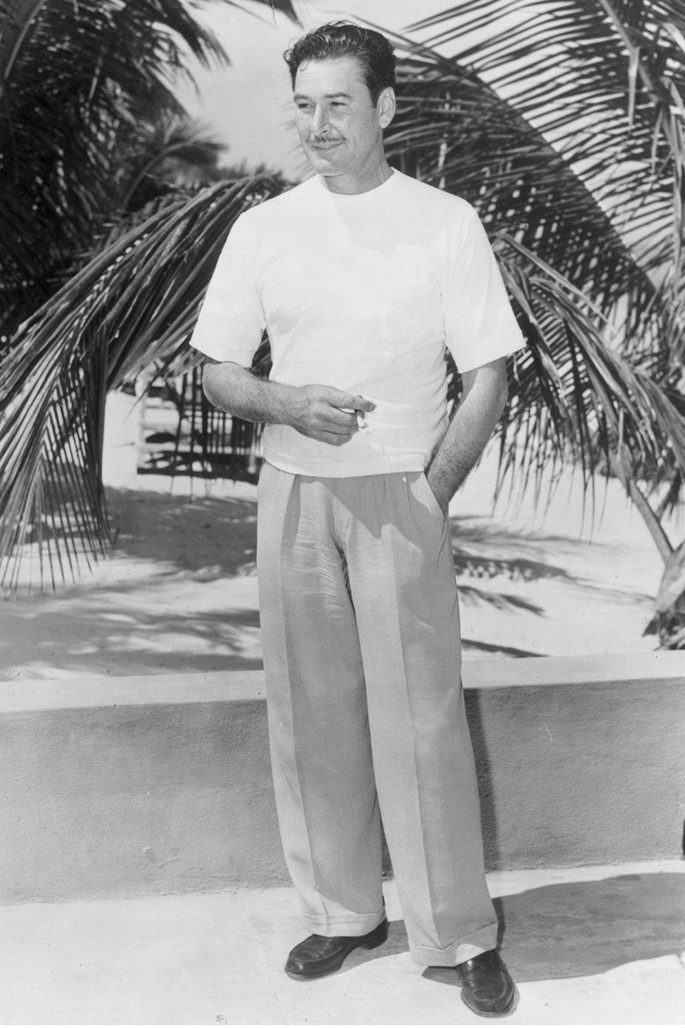 <p>Errol Flynn takes a smoke break while basking in his tropical surroundings.</p>