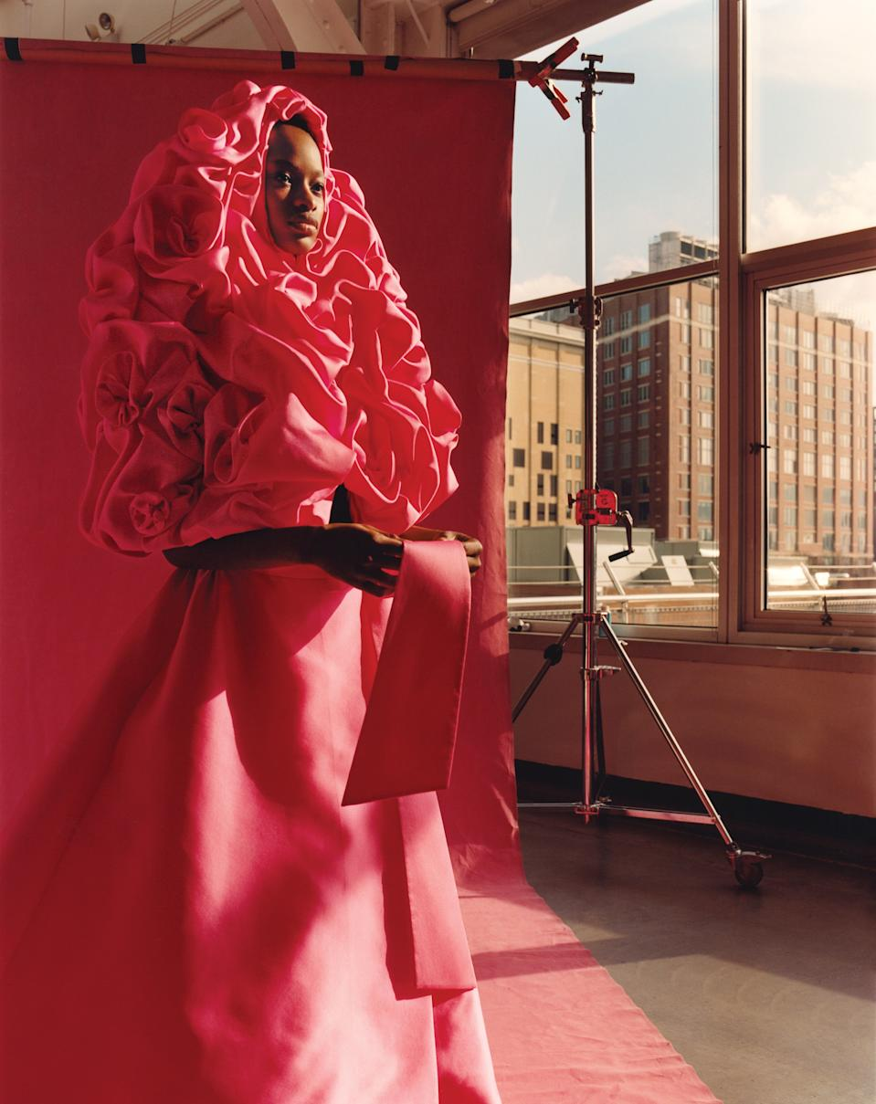 Model Mayowa Nicholas in the rose-scattered cape and skirt that opened Valentino's spring 2019 haute couture collection. Fashion Editor: Camilla Nickerson. Hair: James Pecis; Makeup: Dick Page; Manicure: Megumi Yamamoto. Produced by Alexis Piqueras for Rosco Production.