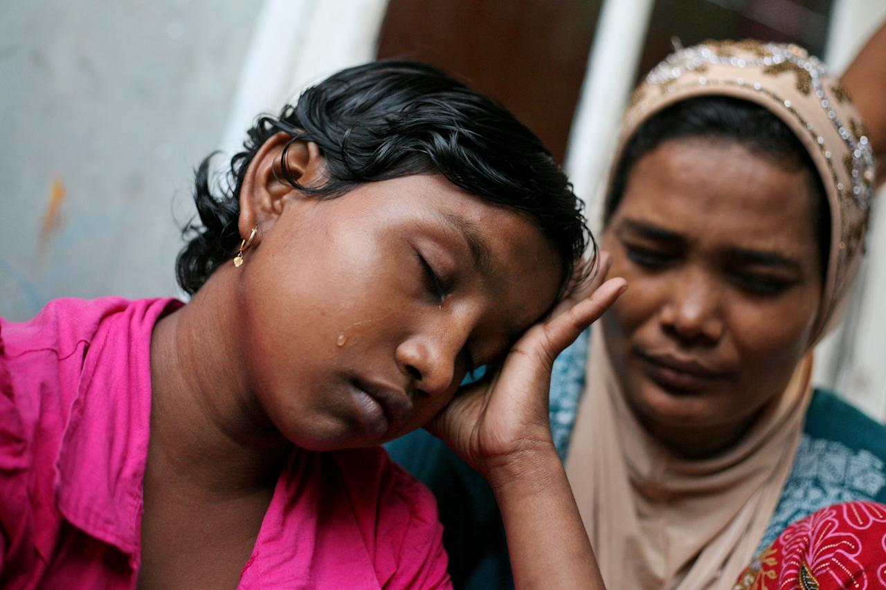 In this Oct. 19, 2013 photo, young ethnic Rohingya asylum seeker Senwara Begum, left, cries at a temporary shelter in Medan, North Sumatra, Indonesia after making a phone call to her family in Myanmar. After her tiny Muslim village in Myanmar's northwest Rakhine had been destroyed in a fire set by an angry Buddhist mob, she and her brother became separated from their family. (AP Photo/Binsar Bakkara)