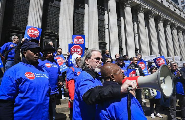 """Kevin Walsh, center, New York Metro Area Postal Union director, holds a bullhorn for Eleanor Bailey, a 35-year postal retiree, as she speaks during a rally of postal union members, Thursday April 24, 2014 in New York. Post office workers marched and chanted """"Stop Staples, the U.S. mail is not for sale,"""" to protest against a deal between the postal service and Staples they say will replace living-wage postal jobs with low-wage jobs at Staples. (AP Photo/Bebeto Matthews)"""