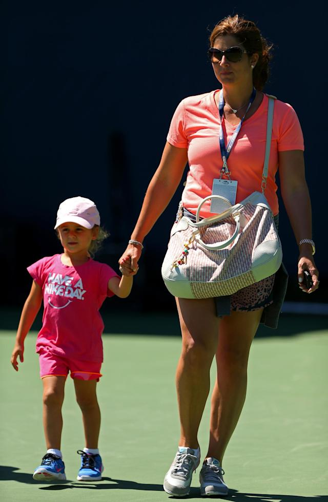 NEW YORK, NY - AUGUST 24: Mirka Federer leaves the practice courts with one of her children after watching her husband Roger Federer of Switzerland during a practice session ahead of the 2013 US Open at USTA Billie Jean King National Tennis Center on August 24, 2013 in New York City. (Photo by Dan Istitene/Getty Images for the USTA)