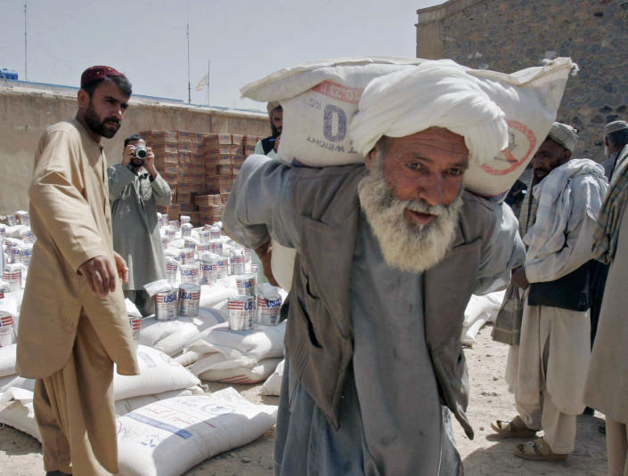 """FILE - In this May 10, 2009 file photo, a man carries a sack of wheat distributed to poor displaced families, distributed by World Food Program with the cooperation of United Nations Assistance Mission in Afghanistan and the United States Agency for International Development, in Kandahar Afghanistan. After 20 years America is ending its """"forever"""" war in Afghanistan. With a poverty rate of 54 per cent, which means the majority of Afghans are living on $1.90, the majority of Afghans hold out little hope for their future according to a 2018 Gallup poll. (AP Photo/Allauddin Khan, File)"""