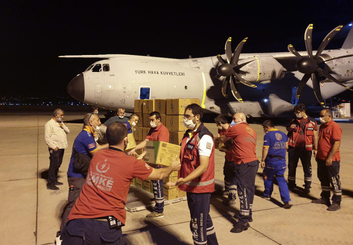 In this photo provided by Turkish Defense Ministry, rescue workers load boxes into a cargo plane at a military airport near Ankara, Turkey, late Wednesday, Aug. 5, 2020. Turkey sent rescue teams and aid to Beirut after an explosion in the Lebanese capital's port killed more than 100 people and injured thousands on Tuesday. (Turkish Defense Ministry via AP, Pool)