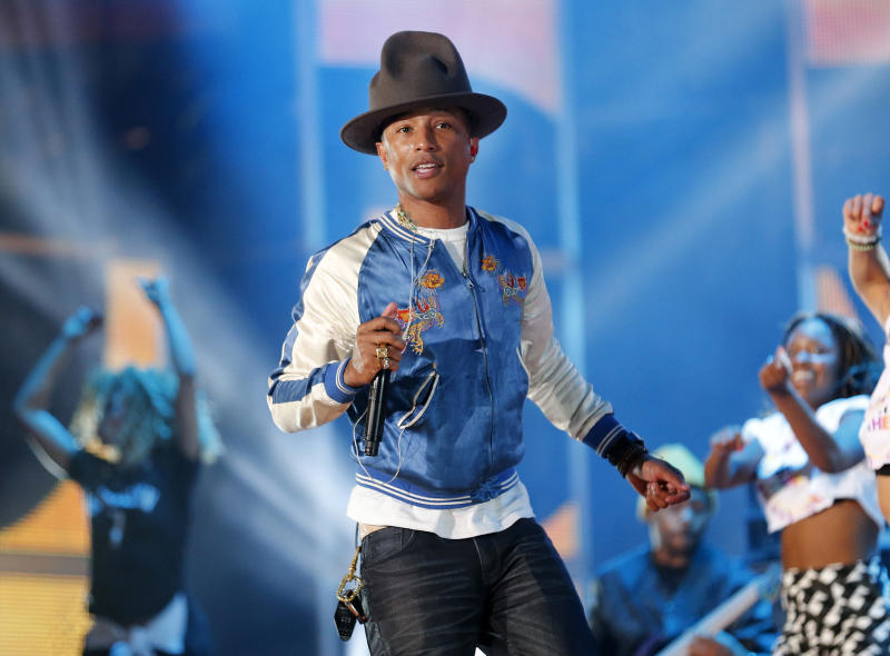 "FILE - This Feb. 16, 2014 file photo shows singer-producer Pharrell Williams rehearsing before the NBA All Star basketball game in New Orleans. This week Pharrell released his sophomore solo album, ""G I R L,"" which features the Oscar-nominated hit, ""Happy."" The song is spending its second week on top of the Billboard Hot 100 chart. (AP Photo/Bill Haber, File)"
