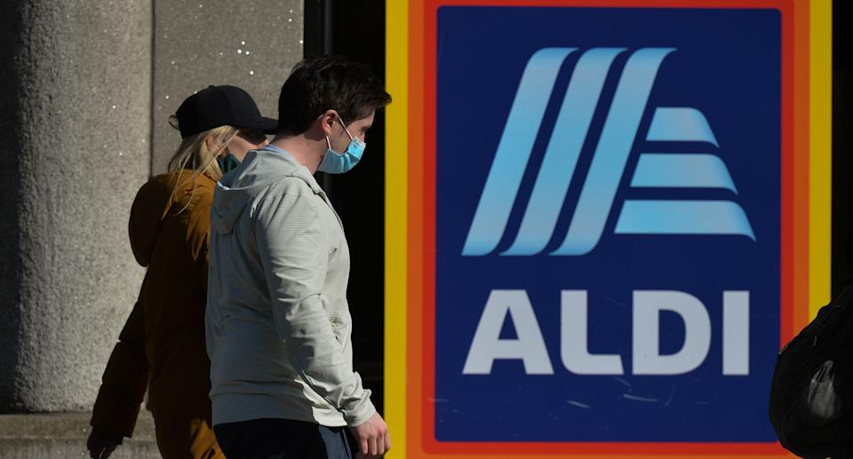 People wearing face masks walk past the ALDI logo. Source: Getty Images
