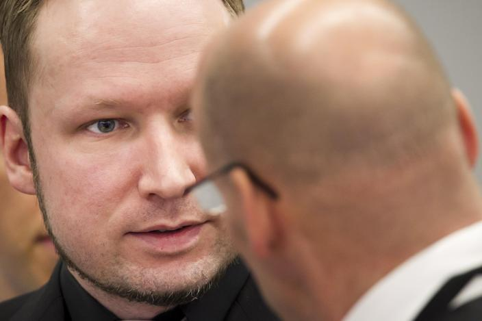 Defendant Anders Behring Breivik, centre, talks to an unidentified official in court at the start of the 5th day of his mass killing trial in Oslo, Norway, Friday April 20, 2012. Confessed mass murderer Breivik testified Thursday in a chilling account of his preparations for the massacre of 77 people. (AP Photo / Heiko Junge, POOL)