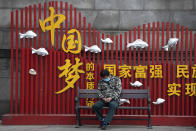 """A resident naps near government propaganda which reads """"China Dream"""" in Wuhan in central China's Wuhan province on Wednesday, April 1, 2020. Skepticism about China's reported coronavirus cases and deaths has swirled throughout the crisis, fueled by official efforts to quash bad news in the early days and a general distrust of the government. In any country, getting a complete picture of the infections amid the fog of war is virtually impossible. (AP Photo/Ng Han Guan)"""