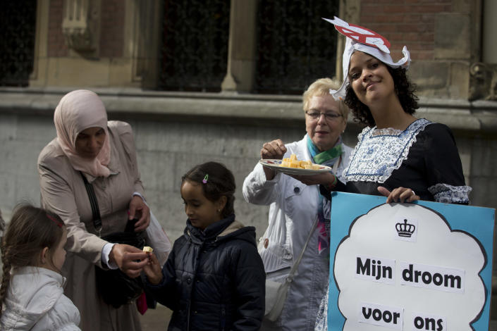 A women gives children some cheese handed out by a protester urging for a ban on nuclear bombs during the opening of the new parliamentary year in The Hague, Netherlands, Tuesday, Sept. 17, 2013. King Willem-Alexander outlined the government's plan and budget policies for the year ahead. (AP Photo/Peter Dejong)