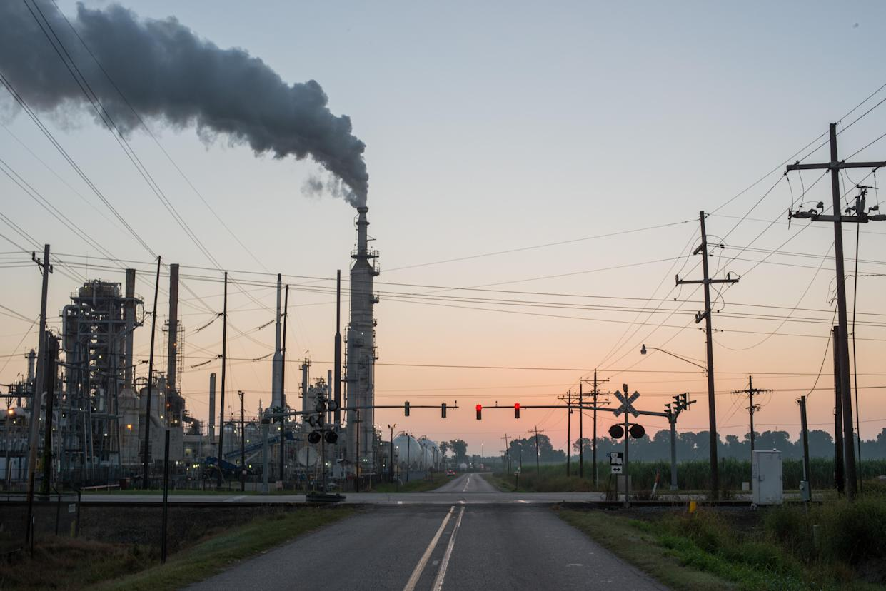 """Smoke billows from one of many plants near what some call """"Cancer Alley,"""" which lies along the once pristine Mississippi River that stretches some 80 miles from New Orleans to Baton Rouge, La., where a dense concentration of oil refineries, petrochemical plants and other chemical industries reside alongside suburban homes. (Photo: Giles Clarke/Getty Images)"""