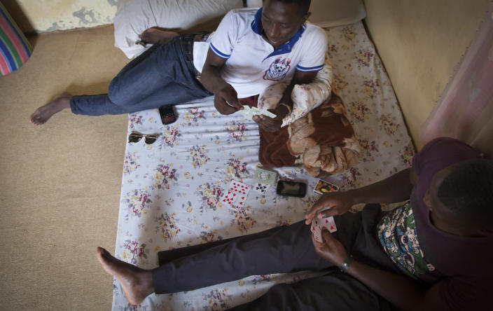 """In this photo taken Tuesday, March 25, 2014, two Ugandan homosexuals play cards in the one-room safe-house where they now live, at an undisclosed location in Uganda. The enactment of Uganda's new anti-gay law has spread fear among homosexuals, forcing many to flee to so-called """"safe houses"""", often single rooms that are more likely to be locked up day and night because of safety concerns. (AP Photo)"""