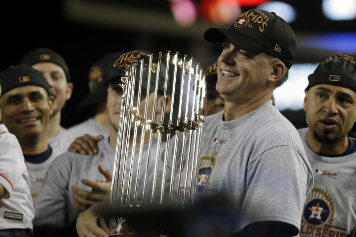 FILE - In this Nov. 1, 2017, file photo, Houston Astros manager A.J. Hinch holds the championship trophy after Game 7 of baseball's World Series against the Los Angeles Dodgers, in Los Angeles. Houston manager AJ Hinch and general manager Jeff Luhnow were suspended for the entire season Monday, Jan. 13, 2020, and the team was fined $5 million for sign-stealing by the team in 2017 and 2018 season. Commissioner Rob Manfred announced the discipline and strongly hinted that current Boston manager Alex Cora — the Astros bench coach in 2017 — will face punishment later. Manfred said Cora developed the sign-stealing system used by the Astros. (AP Photo/Matt Slocum, File)