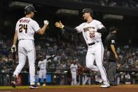 Arizona Diamondbacks' Pavin Smith (26) and Luke Weaver (24) celebrate their runs scored against the Miami Marlins during the third inning of a baseball game Monday, May 10, 2021, in Phoenix. (AP Photo/Ross D. Franklin)