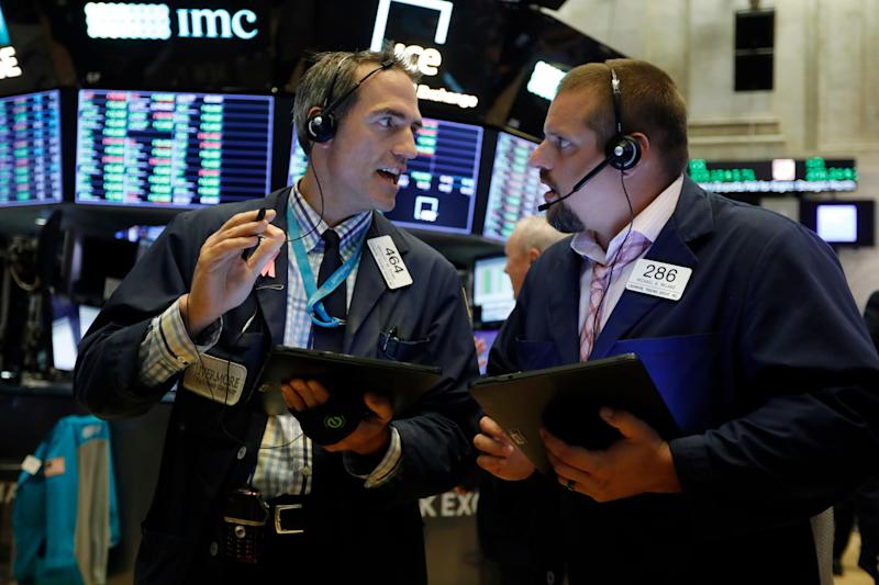 In this Aug. 19, 2019, file photo traders Gregory Rowe, left, and Michael Milano work on the floor of the New York Stock Exchange.