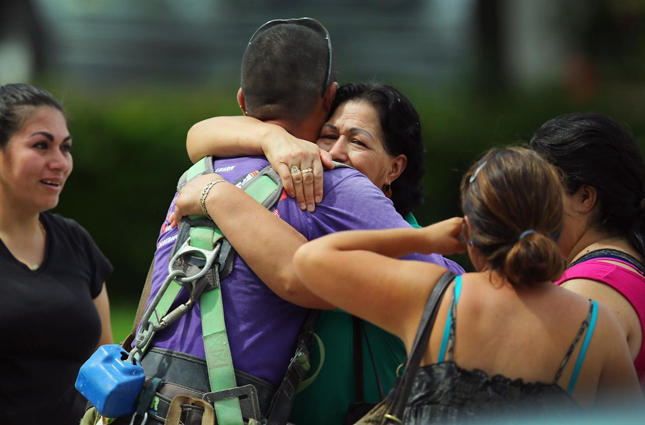 Family members hug a construction worker who was working on a four-story parking garage that was under construction and collapsed at the Miami Dade College?s West Campus on October 10, 2012 in Doral, Florida.  Early reports indicate that one person was killed, at least seven people injured and an unknown number of people may be buried in the rubble.  (Photo by Joe Raedle/Getty Images)