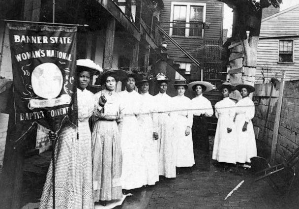 PHOTO: Nine African-American women pose for a photo with Nannie Burroughs, holding a banner that reads, 'Banner State Woman's National Baptist Convention,' circa 1905. (Library of Congress)