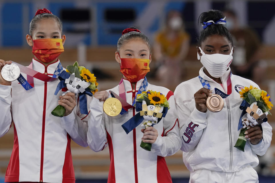 Gold medalist Guan Chenchen (center), of China, stands on the podium with silver medalist Tang Xijing (left), of China, and bronze medalist Simone Biles, of the U.S., after balance beam competition during the artistic gymnastics women's apparatus final at the 2020 Summer Olympics, on Aug. 3 in Tokyo. (AP Photo/Gregory Bull) - Credit: AP