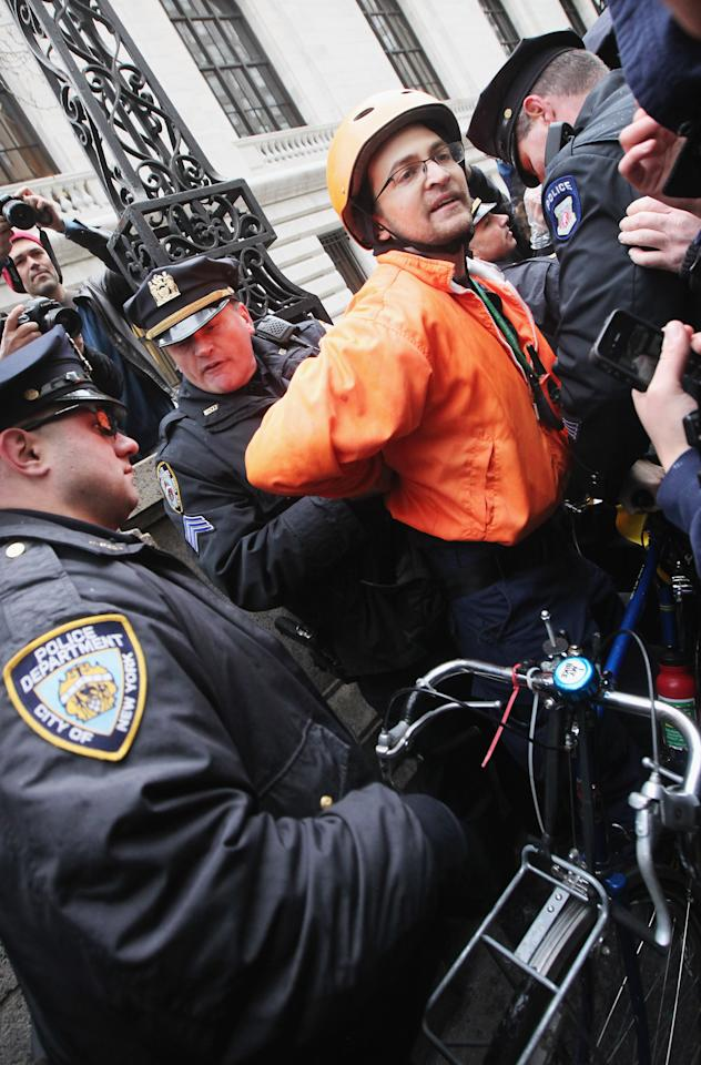 """NEW YORK, NY - FEBRUARY 29:  A protester is arrested by NYPD during an Occupy Wall Street """"Shut Down the Corporations"""" protest on February 29, 2012 in New York City. Occupy movements across the country are planning protests in dozens of cities against corporate power.  (Photo by Mario Tama/Getty Images)"""