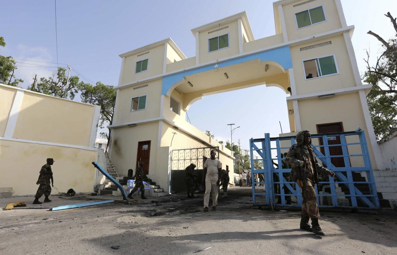 Somali government soldiers walk outside the Presidential palace after an attack in the capital Mogadishu July 9, 2014. Islamist militants attacked Somalia's presidential compound on Tuesday with a car bomb and gunmen broke through a perimeter wall but were repulsed by security forces, and the president was not there at the time, the interior ministry said. REUTERS/Feisal Omar (SOMALIA - Tags: CIVIL UNREST POLITICS CRIME LAW)