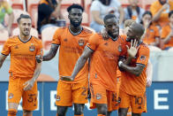 Houston Dynamo's Maximiliano Urruti (37) and Derrick Jones (21) look on as Maynor Figueroa (15) and Fafa Picault (10) celebrate a goal by Picault against the Portland Timbers during the first half of an MLS soccer match Wednesday, June 23, 2021, in Houston. (AP Photo/Michael Wyke)