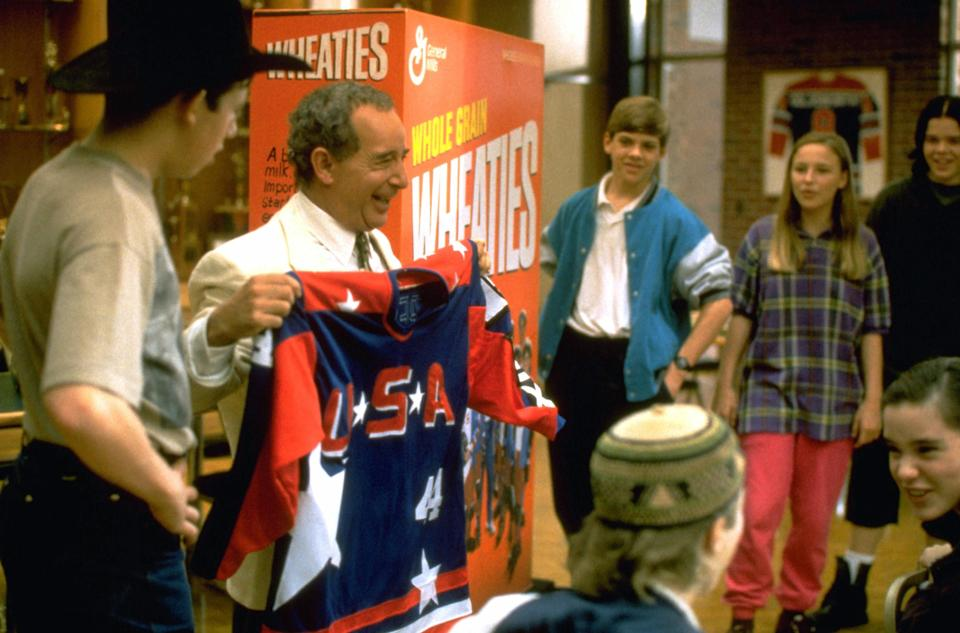 man holding up a hockey jersey in front of kids