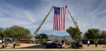 The last few vehicles which participated in the law enforcement funeral procession for Drug Enforcement Administration Supervisory Agent Michael G. Garbo travel under a large American Flag while entering the parking lot of Calvary Chapel in Tucson, Ariz. on Friday, Oct. 8, 2021. Garbo, a federal agent shot and killed while questioning a passenger on an Amtrak train in Arizona, was remembered Friday as a venerated leader and mentor with an unparalleled work ethic. (Rebecca Sasnett/Arizona Daily Star via AP)