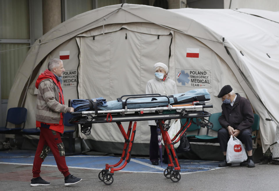 A member of the medical staff transports a stretcher past a medical tent used for COVID-19 testing near a hospital in Warsaw, Poland, on Wednesday, Nov. 4, 2020. Poland hit a daily high of nearly 24,700 coronavirus cases as the government introduced new restrictions in shops, schools and culture institutions through November. (AP Photo/Czarek Sokolowski)