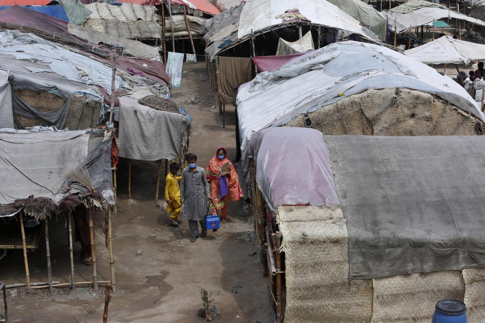 Health workers visit a slum area for polio vaccination, in Lahore, Pakistan, Saturday, Aug. 15, 2020. Pakistani government launched an anti-polio vaccination campaign in an effort to eradicate the crippling disease affected children. (AP Photo/K.M. Chaudary)