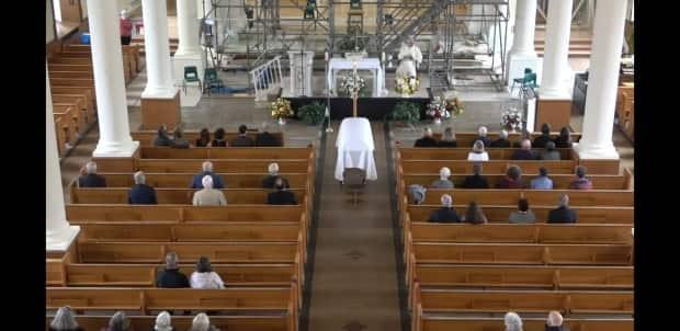 A limited number of mourners are shown at a funeral at St. Ninian Cathedral in Antigonish. (C.L. Curry Funeral Services - image credit)