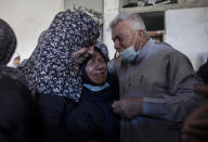 Palestinian relatives mourn over the bodies of four brothers from the Tanani family that werer found under the rubble of a destroyed house following Israeli airstrikes in Beit Lahiya, northern Gaza Strip, Friday, May 14, 2021. (AP Photo/Khalil Hamra)