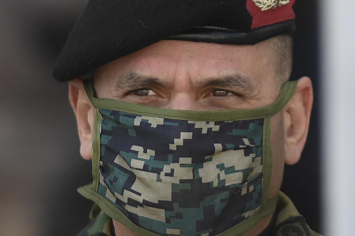Adm. Remigio Ceballos wears a camouflage face mask as he supervises the unloading of humanitarian aid from China at Maiquetia International Airport amid the spread of the new coronavirus in La Guaira, Venezuela, Saturday, March 28, 2020. (AP Photo/Matias Delacroix)