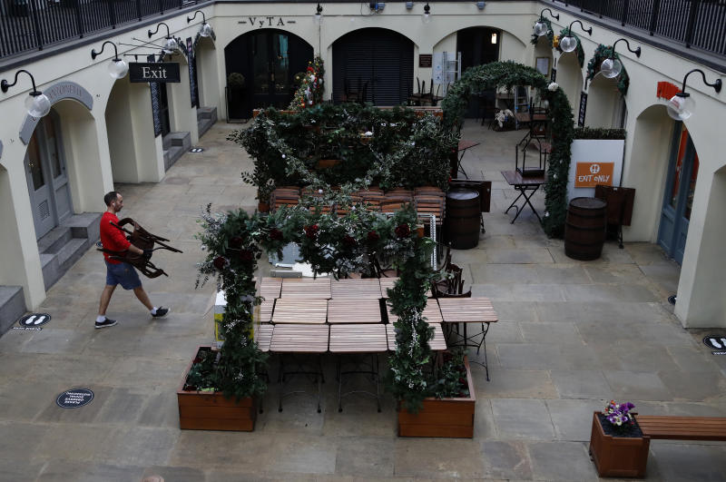 An owner of a restaurant starts preparing the outdoor seating for the reopening at Covent Garden in London, Tuesday, June 30, 2020. Tuesday marked 100 days since Britain's Prime Minister Boris Johnson detailed a short list of reasons why individuals could leave their homes as he ordered the immediate closure of all shops selling non-essentials. (AP Photo/Frank Augstein)