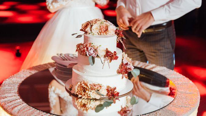 Beautiful delicious white wedding cake ceremony at the table.
