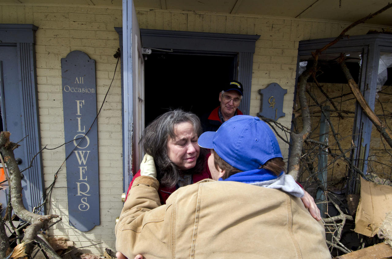 Linda Oakley hugs a friend at her demolished flower shop Monday, March 5, 2012, as her husband, Dale, looks on in West Liberty, Ky. She later handed out flowers to volunteer workers who are helping with the cleanup from Friday's tornado. (AP Photo/John Flavell)